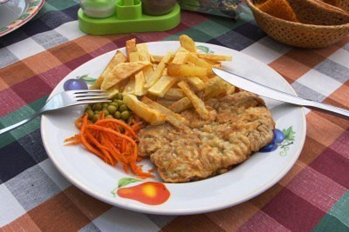 991383 cotoletta di pollo patatine fritte e verdure su un piatto una forchetta e un coltello