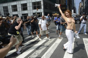 Activist Karen Heaven is followed by photographers as she marches in a rally, to protest for the right of women to go topless anywhere a man is able to, in New York
