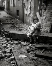 Una bambina con la sua bambola siede sulle macerie della propria casa bombardata, Londra, 1940
