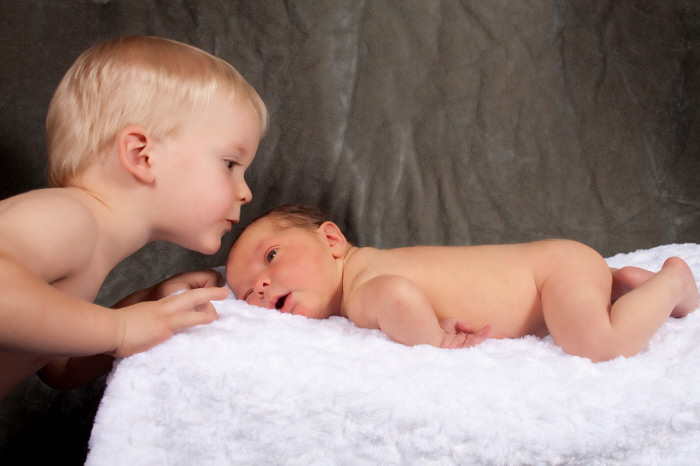 A two year old boy kisses his newborn baby brother