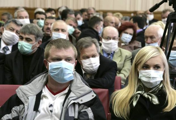 Participants of the Ministers' Cabinet session wear masks as they listen to Ukraine's Prime Minister Yulia Tymoshenko in Ternopil in western Ukraine