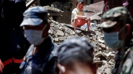 A young boy watches from a mound of rubble as a search and rescue team from the Royal Thai Armed Forces digs at the entrance to where a home used to stand in search for the owner's body in Sankhu, after the devastating earthquake that hit the country on 25 April 2015, Kathmandu, Nepal, 03 May 2015. According to Nepalese officials, four survivors were rescued in northern Nepal, eight days after the earthquake hit the Himalayan country. The government updated the confirmed official death toll to 7,040, as reports of rescue workers digging out more dead bodies from the rubble in rural villages continue to pour in.  ANSA/DIEGO AZUBEL