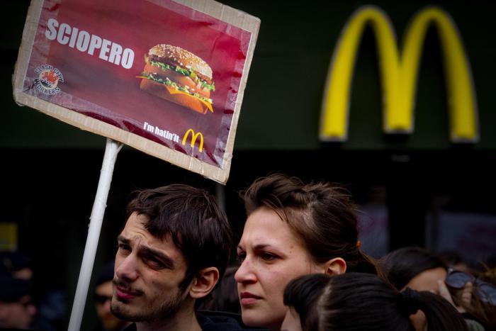 In occasione della festa della donna il presidio di solidarietà per tutte le donne e i lavoratori del McDonald's di piazza Municipio a Napoli dove ci sono stati momenti di tensione con la polizia costretta in tenuta antisommossa a presidiare l'ingresso del fast food, 8 marzo 2014. ANSA / CIRO FUSCO