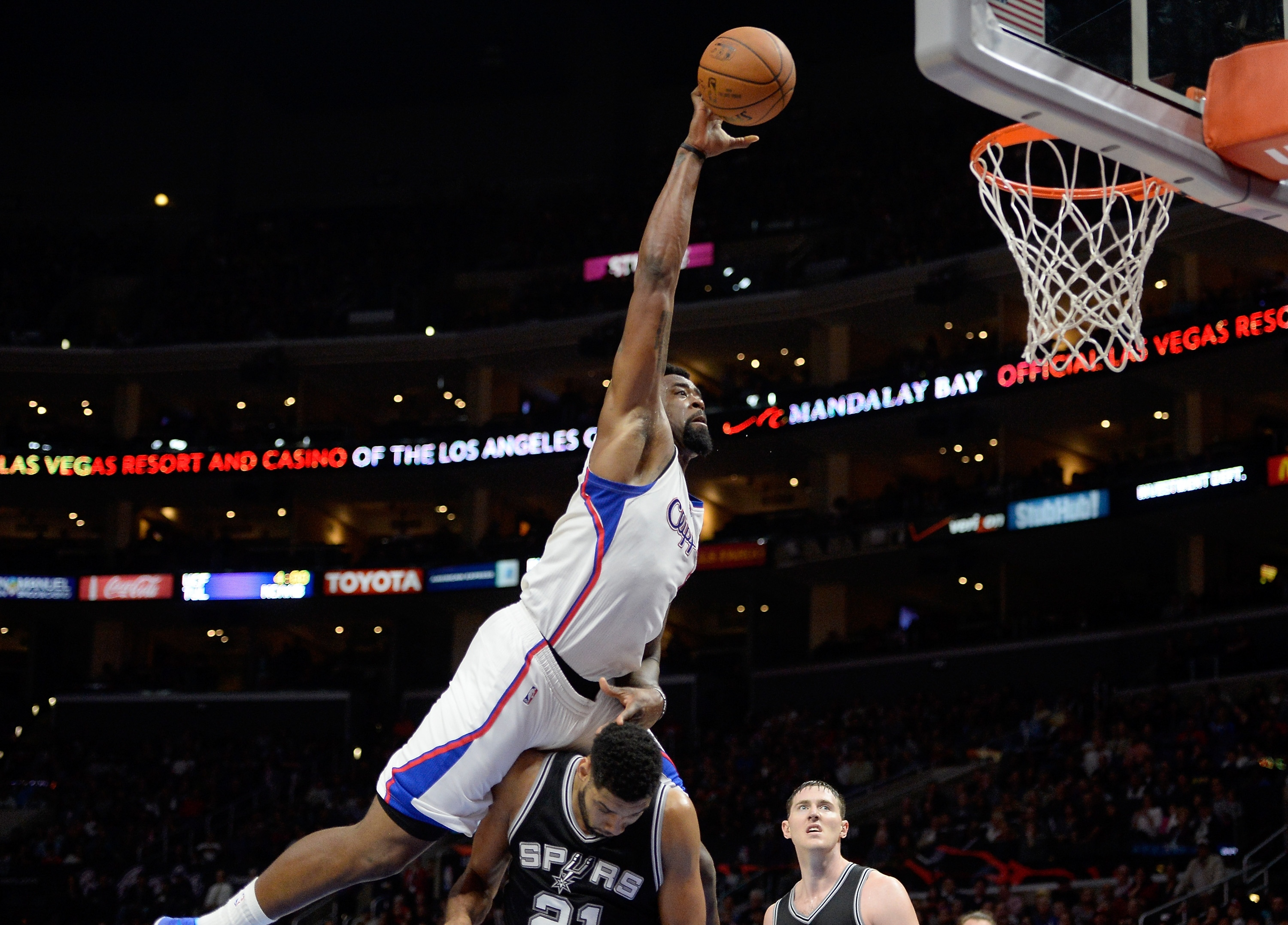 LOS ANGELES, CA - FEBRUARY 19:  DeAndre Jordan #6 of the Los Angeles Clippers is fouled by Tim Duncan #21 of the San Antonio Spurs on an attempted dunk at Staples Center on February 19, 2015 in Los Angeles, California.  NOTE TO USER: User expressly acknowledges and agrees that, by downloading and or using this Photograph, user is consenting to the terms and condition of the Getty Images License Agreement.  (Photo by Harry How/Getty Images)