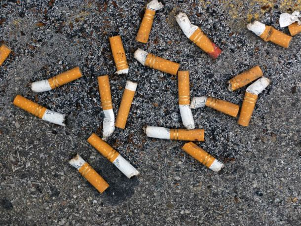 25 Jan 2012, Pewaukee, Wisconsin, USA --- Cigarette butts litter the asphalt of a parking lot. --- Image by © Paul Damien/National Geographic Creative/Corbis