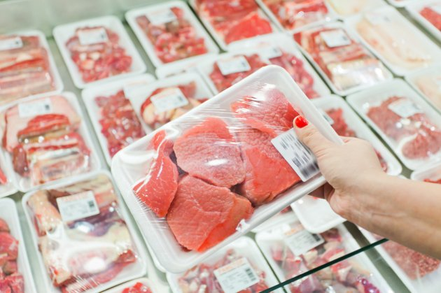 Image of packaged meat with woman hand in the supermarket