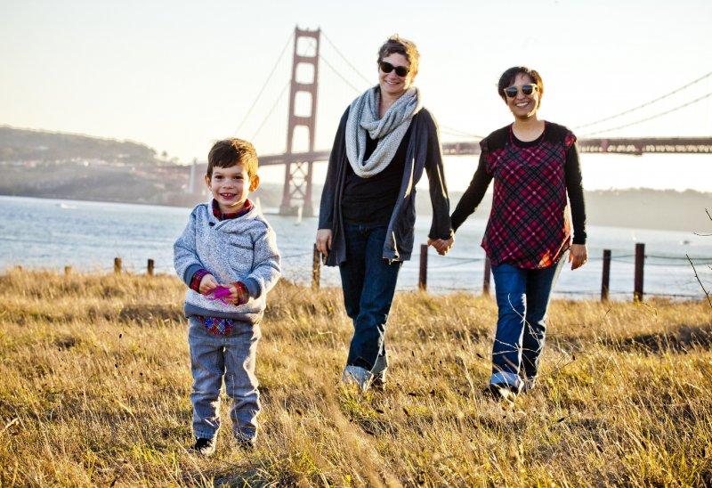 Un bambino passeggia felice con le sue due mamme