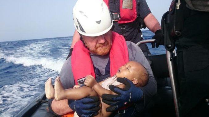 La foto shock divulgata da Sea Watch che ritrae il corpo senza vita di un bimbo di circa un anno tra le braccia di un soccorritore.