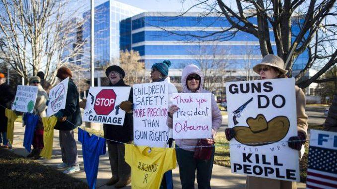 USA: un gruppo di manifestanti sventola cartelli contrari alla vendita delle armi, legale in tutti gli Stati Uniti d'America