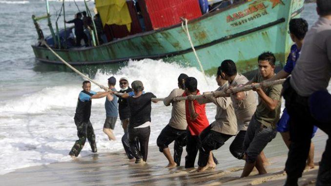 Un gruppo di migranti traina una barca a riva