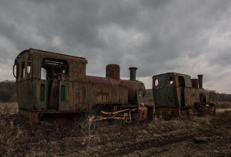 Un vecchio treno resta di vedetta sui campi spogli.