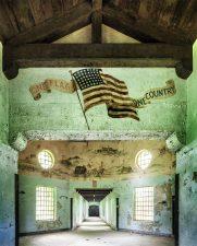 Murales di una bandiera americana che svetta orgogliosamente sull'abbandono.
