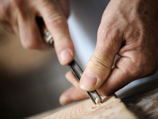 hands of the craftsman carve a bas-relief with a gouge