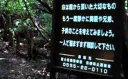 Il cartello all'inizio del sentiero che conduce nella foresta. Il messaggio in giapponese esorta chi cammina a non procedere, e a pensare alla propria famiglia.