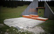 Il podio di Sarajevo giace solitario, un monumento in una distesa d'erba.