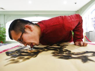Folk artist Han Xiaoming demonstrates painting with his tongue in Hangzhou, Zhejiang province December 4, 2014. Han dips his tongue in ink to paint on paper, and uses his fingers to fill in final adjustments. The artist also uses a paintbrush held with his mouth and utilizes fish and vegetables as paint tools, local media reported. REUTERS/Aly Song (CHINA - Tags: SOCIETY TPX IMAGES OF THE DAY)