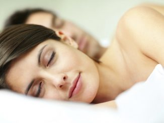 Closeup portrait of a lovely young female sleeping on the bed with her husband