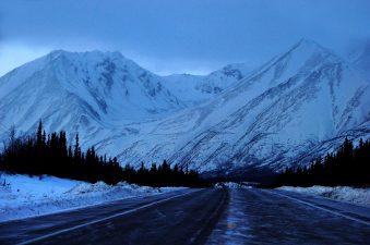 Una strada innevata di fronte alle montagne dellAlaska.