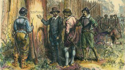 """White e i suoi uomini davanti alla scritta """"CROATOAN"""""""