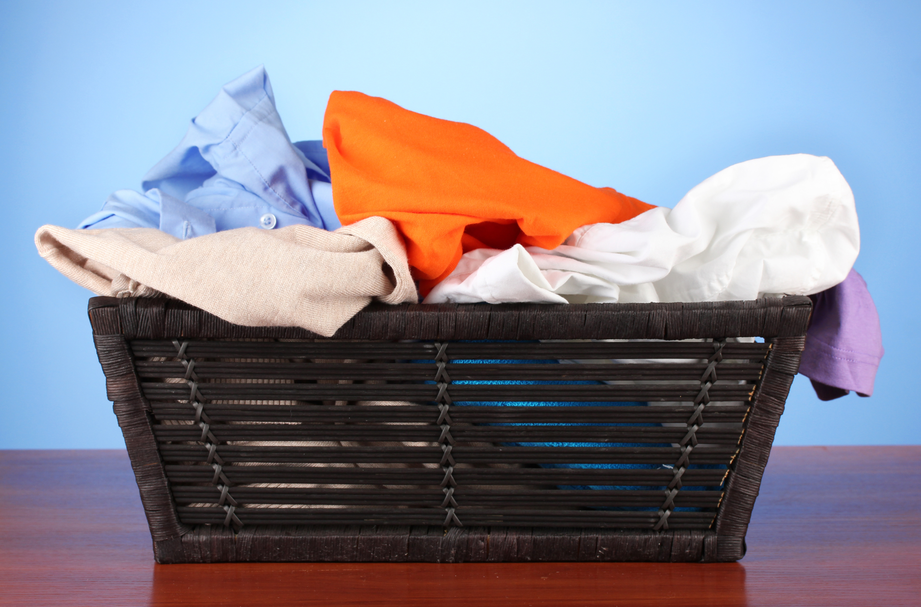 Bright clothes in laundry basket, on color background