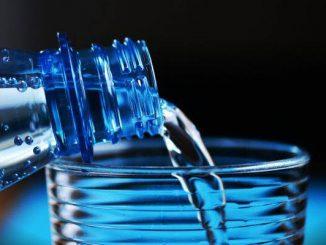 Acqua versata da una bottiglia in un bicchiere.