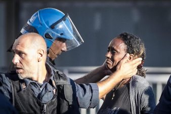 Un poliziotto conforta migrante sgomberata