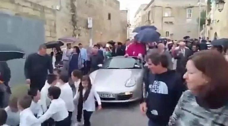 Arcivescovo su una Porsche trainata da 50 bambini