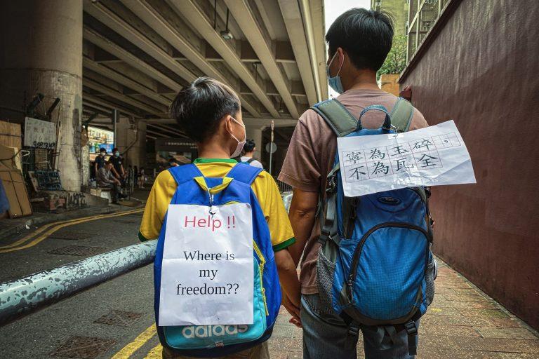 Piccoli manifestanti protestano con i cartelli sugli zaini