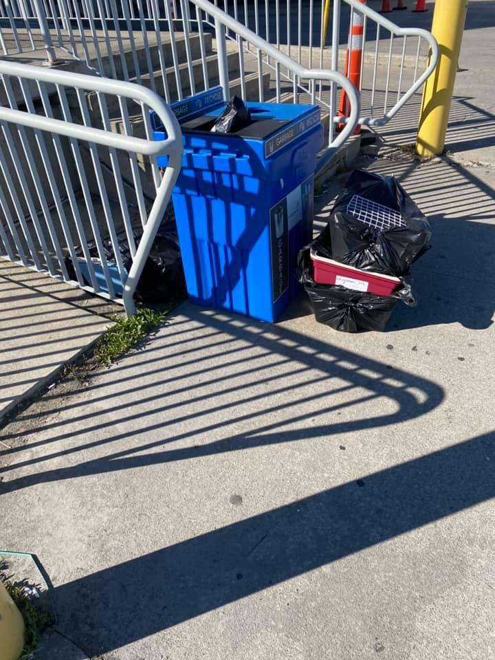 La gabbia accanto un bidone della spazzatura