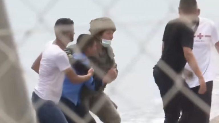 Un migrante aiutato da un soldato a Ceuta